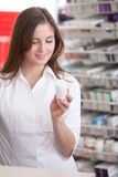 Female Pharmacist Reading Information On Medicine Stock Photography
