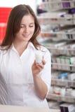 Female Pharmacist Reading Information On Medicine Stock Photography