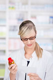 Female pharmacist reading the prescription Royalty Free Stock Photography
