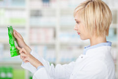 Female Pharmacist Reading Product Details In Pharmacy Stock Image