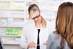 Female pharmacist reads a medicine prescription Royalty Free Stock Images
