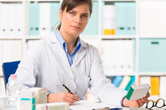 Female pharmacist sat at desk writing notes. Half body portrait of attractive young female pharmacist in white coat sat at desk writing notes with boxes of Royalty Free Stock Photos
