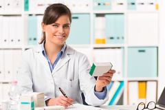 Female pharmacist sat at desk writing notes. Half body portrait of Smiling young female pharmacist in white coat sat at desk writing notes with boxes of medicine Stock Photo