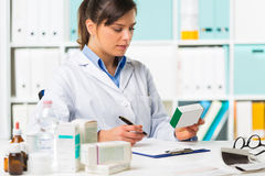 Female pharmacist sat at desk writing notes. Pretty young smiling female doctor sat at desk writing notes with boxes of medicine in foreground Stock Images