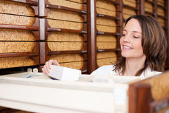 Female Pharmacist Searching Medicines. Mid adult female pharmacist searching medicines at stockroom Royalty Free Stock Image