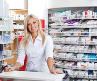 Female Pharmacist Standing at Checkout Counter. Portrait of smiling female pharmacist standing at checkout counter royalty free stock photos