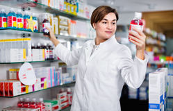 Female pharmacist suggesting useful body care products. Diligent friendly female pharmacist suggesting useful body care products in pharmacy royalty free stock image