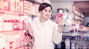Female pharmacist suggesting useful body care products. Young friendly female pharmacist suggesting useful body care products in pharmacy stock photography