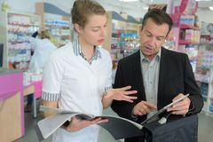 Female pharmacist talking to commercial. Female pharmacist talking to a commercial Royalty Free Stock Images