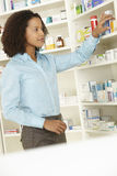 Female pharmacist working in UK pharmacy Royalty Free Stock Images