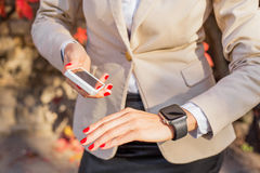 Female with phone and smartwatch Stock Images