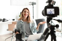 Female photo blogger recording video on camera. Indoors royalty free stock photography