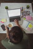 Female photo editor holding coffee cup while using laptop in office Royalty Free Stock Images