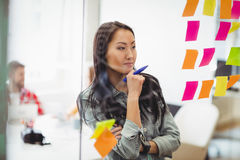 Female photo editor looking at multi colored sticky notes. On glass in meeting room at creative office stock image