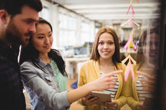 Female photo editor standing near coworkers pointing on sticky note. Portrait of smiling female photo editor standing near coworkers pointing on sticky note in Royalty Free Stock Images