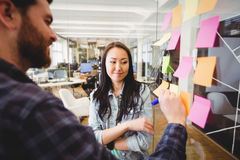 Female photo editor standing near male coworker writing on sticky note. In meeting room Stock Image
