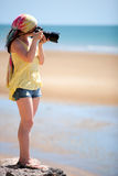 Female photographer. Beautiful young female photographer taking pictures on beach Royalty Free Stock Image