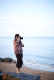 Female photographer. Beautiful young female photographer taking pictures on beach Royalty Free Stock Photography