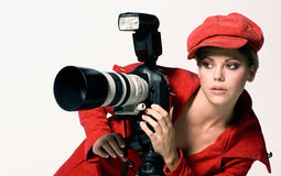 Female photographer. With red coat and cap Stock Photos