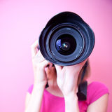 Female photographer. Pointing her super wide lens at you (color toned image Royalty Free Stock Photo