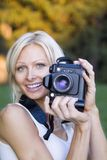 Female photographer. Young blond woman holding camera outdoors stock images
