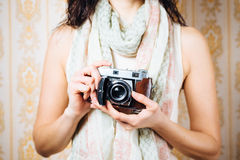 Female photographer artist with old camera. Hipster woman taking photos with retro film camera on vintage ornamental wall background Royalty Free Stock Photos
