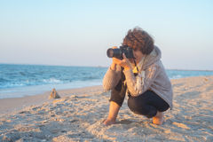 Female photographer on the beach Stock Photography
