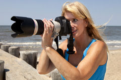 Female Photographer. On the beach taking pictures with a telephoto zoom lens Royalty Free Stock Images
