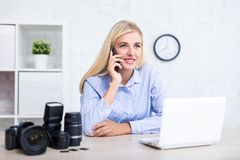 Female photographer with camera, computer and photography equipment talking by phone with clients in office. Female photographer with camera, computer and royalty free stock photos