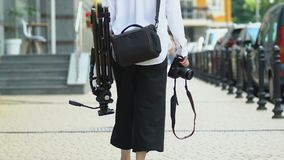 Female photographer carrying camera and tripod with case, professional equipment. Stock footage stock video