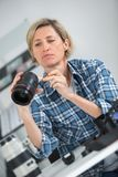 Female photographer cleaning camera lens Royalty Free Stock Photos
