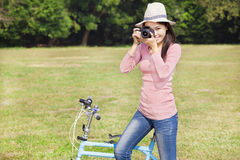 Female photographer holding camera and sitting bike royalty free stock image