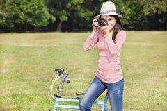 Female photographer holding camera and sitting bike Royalty Free Stock Image