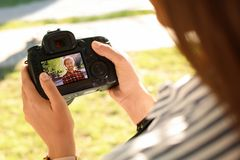 Female photographer holding professional camera with photo of young man on display in park. Closeup stock photography