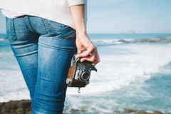 Female photographer holding vintage camera on travel. Female photographer with vintage film camera on vacation travel towards the sea in Asturias, Spain Royalty Free Stock Images