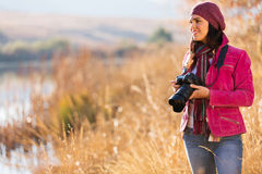 Female photographer outdoors. Young female photographer holding a camera outdoors in autumn Stock Images
