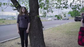 Girl photographer, photographing a woman outdoors, in the park on a cloudy day stock video footage