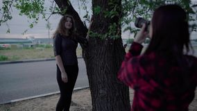 Girl photographer, photographing a woman outdoors, in the park on a cloudy day stock video