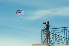 A female photographer in a red cap with a camera stands on the balcony opposite blue sky with clouds and parachute . Woman take pi Royalty Free Stock Photo