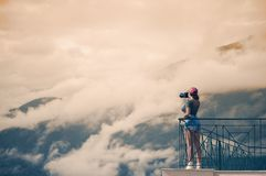 A girl photographer in a red cap with a camera stands on the balcony opposite of Italian mountains and clouds in South Tirol Royalty Free Stock Photo