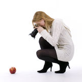 Female photographer shooting red apple Royalty Free Stock Image