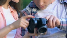 Female photographer showing pictures on camera screen to young man, hobby tips. Stock footage stock footage