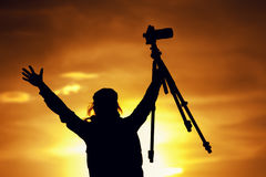 Female photographer silhouette at setting sun. Silhouette of female photographer holding photo camera and tripod at the background of setting sun. Happy woman Royalty Free Stock Photo