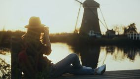 Female photographer sits on a sunset lake pier. Girl with camera takes a photo of traditional old rustic windmill. 4K. stock footage