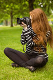 Female photographer sitting on grass Stock Photography