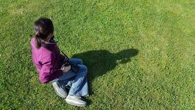 Female photographer using DSLR camera on grass. Female photographer sitting on grass using DSLR camera stock footage