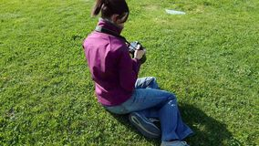 Female photographer using DSLR camera on grass. Female photographer sitting on grass using DSLR camera stock video footage