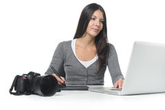 Female photographer smiling as she does her edits Royalty Free Stock Photography