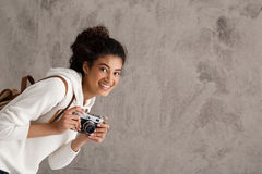 Female photographer smiling, holding camera, looking out over beige background. Stock Photo