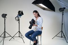 Female Photographer In Studio For Photo Shoot With Camera And Lighting Equipment. Female Photographer In Studio For Photo Shoot With Camera And Lights stock photo